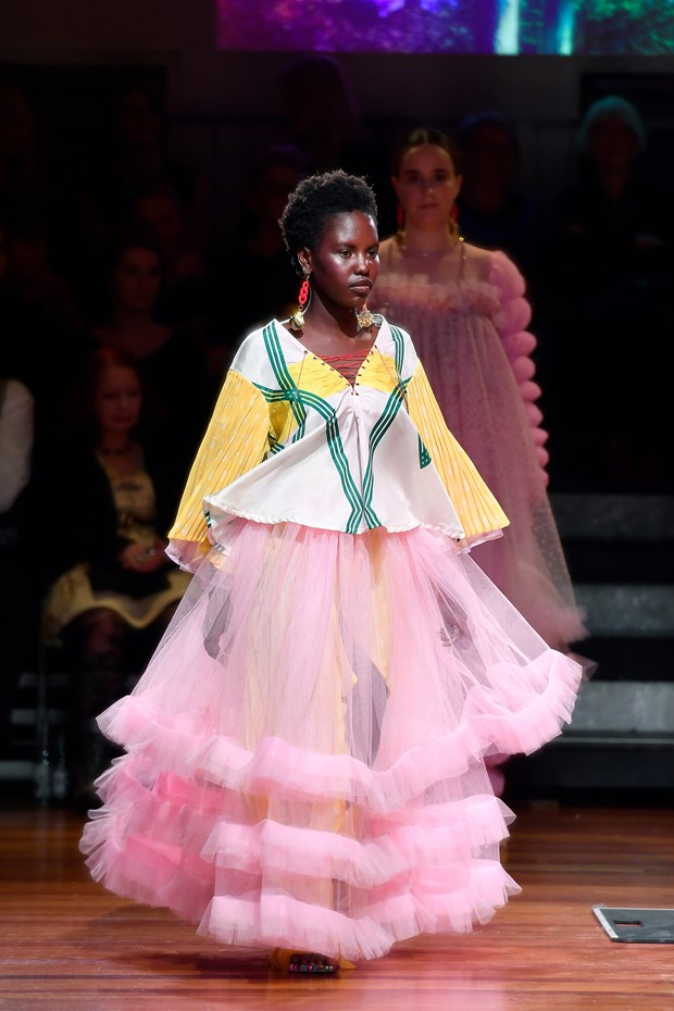 Model wearing layered pink tulle skirt and white and yellow blouse